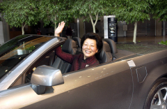 Chinese Vice Minister of Commerce Ma Xiuhong (C) enjoys the drivers seat of a Cadillac XLR