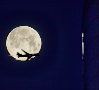 Jet flies past Flower Moon